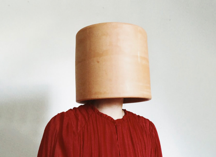 Person wearing a wooden hat.